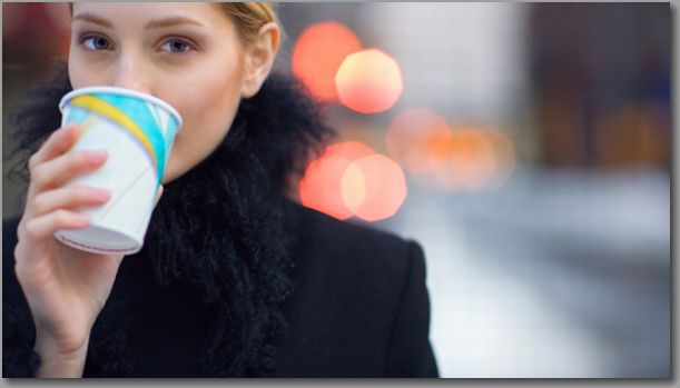 Woman drinking coffee on city sidewalk